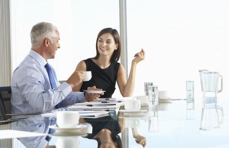 personas hablando: Dos colegas de negocios se sienta alrededor de la sala de reunión de mesa de discusión informal Foto de archivo
