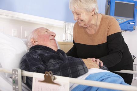 man in hospital bed: Senior woman visiting husband in hospital