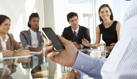 business relationship: Close Up Of Businessman Using Mobile Phone During Board Meeting Around Glass Table Stock Photo