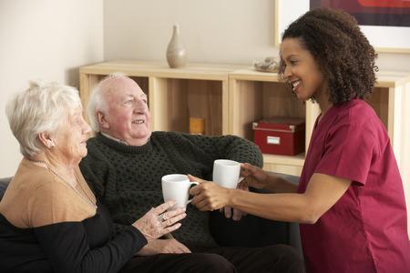 visiting: Nurse visiting senior couple at home
