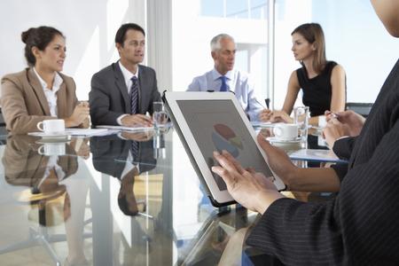 reunion de trabajo: Cierre de negocios que usa la tablilla equipo durante la reunión de la Junta alrededor de la mesa de cristal
