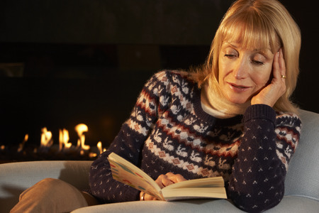 adult woman: Mature woman reading in front of fire at home