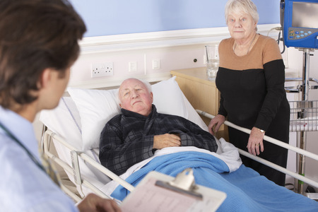 man in hospital bed: Doctor talking to senior couple in hospital Stock Photo