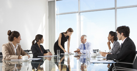 business person: Group Of Business People Having Board Meeting Around Glass Table