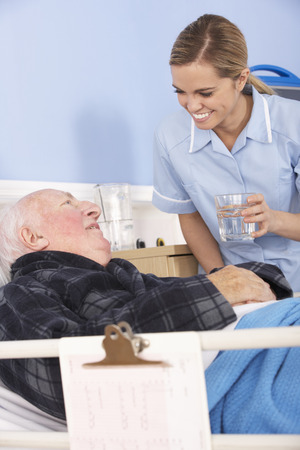 space for copy: Nurse giving glass of water to senior man in hospital