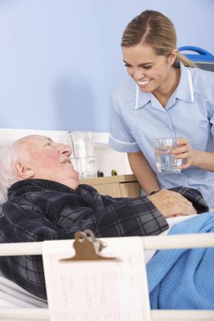 happy nurse: Nurse giving glass of water to senior man in hospital