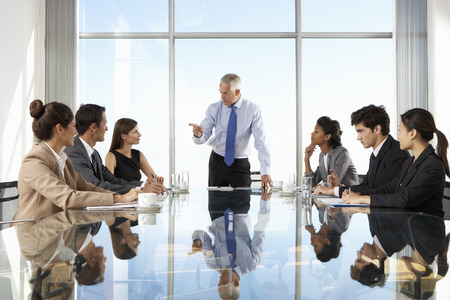 business relationship: Group Of Business People Having Board Meeting Around Glass Table