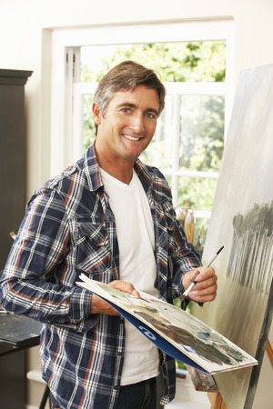 pursuit: Male Artist Working On Painting In Studio Stock Photo