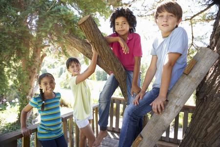 niño trepando: Grupo de niños que cuelgan hacia fuera Treehouse Juntos Foto de archivo