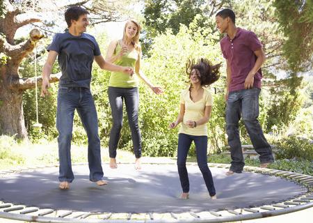 trampoline: Four Teenage Friends Jumping On Trampoline In Garden Stock Photo