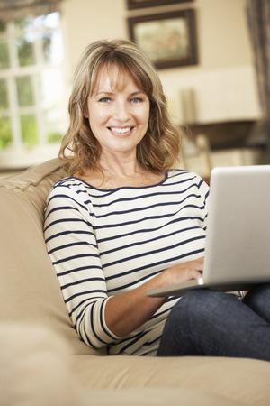 mujer sentada: Madura mujer sentada en el sofá en casa utilizando portátil