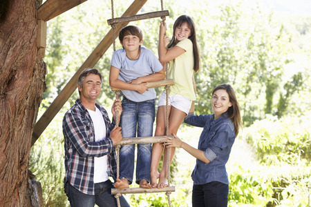 10 year old: Family In Garden By Treehouse Stock Photo