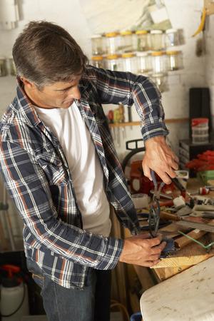 workbench: Man Using Workbench In Garage Stock Photo