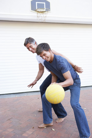 youth sports: Father And Teenage Son Family Playing Basketball Outside Garage Stock Photo