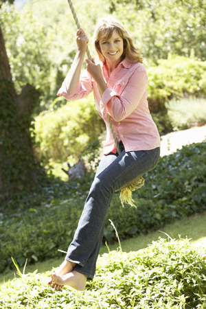 columpios: Mujer envejecida media que se divierte en el oscilación de la cuerda