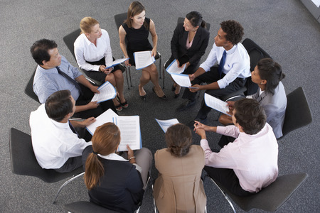 mixed age range: Overhead View Of Businesspeople Seated In Circle At Company Seminar Stock Photo