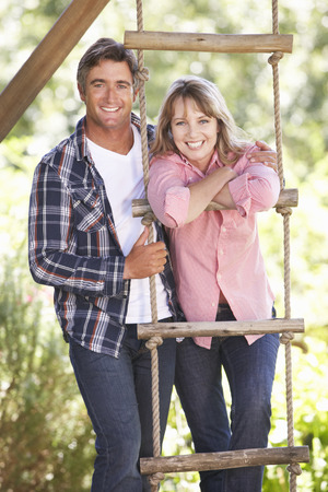 about age: Middle Aged Couple In Garden By Treehouse Stock Photo