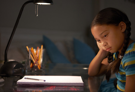 studying: Unhappy Young Girl Studying At Desk In Bedroom In Evening
