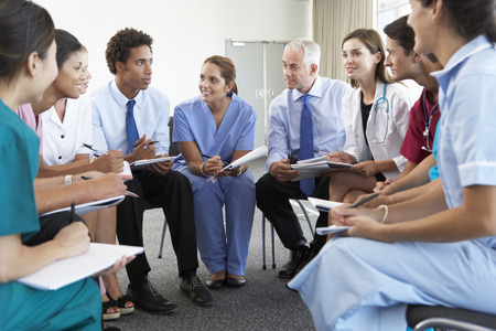 Medicinsk personal sitter i cirkeln vid mål Meeting