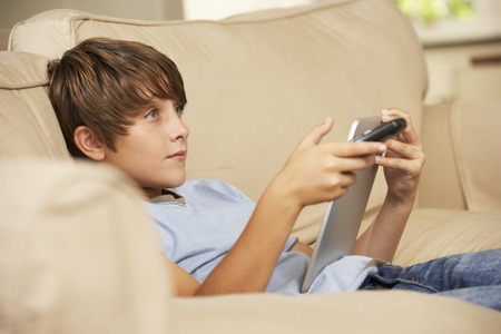 young boy: Young Boy Sitting On Sofa At Home Using Tablet Computer Whilst Watching Television Stock Photo