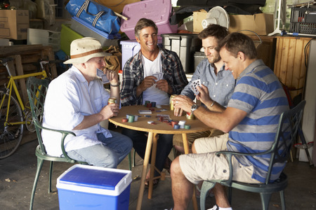 Group Of Male Friends Playing Cards In Garage