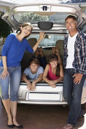 verticales: Familia que se sienta en maletero del coche Foto de archivo