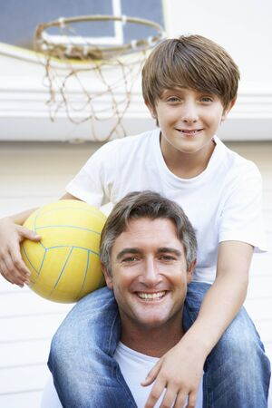 happy families: Father And Son Family Playing Basketball Outside Garage Stock Photo