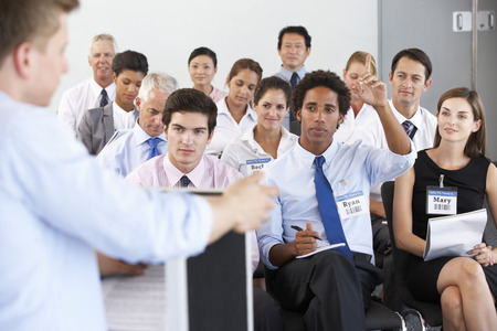 group of business people: Businessman Delivering Presentation At Conference Stock Photo