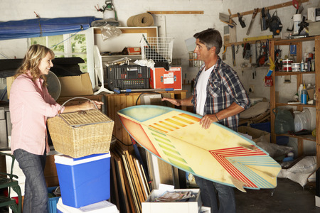 mess: Couple Clearing Garage For Yard Sale Stock Photo