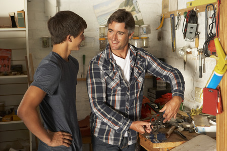 Father Teaching Son To Use Workbench In Garage