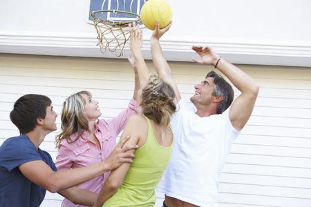 baloncesto chica: Familia adolescente que juegan al baloncesto Garaje exterior Foto de archivo