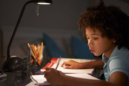 11 year old: Young Boy Studying At Desk In Bedroom In Evening