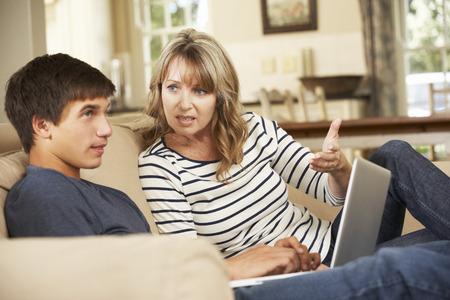 adolescente: Madre e hijo adolescente que discuten en el sofá en casa Foto de archivo