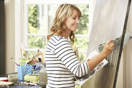 middle age woman: Female Artist Working On Painting In Studio