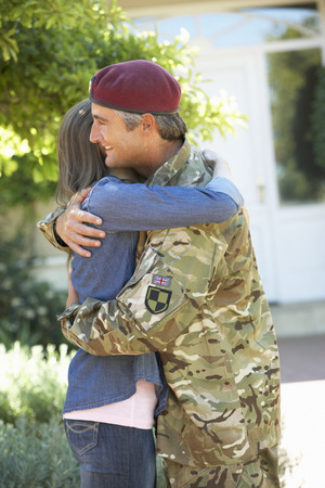 coming together: Soldier Returning Home And Greeted By Wife Stock Photo
