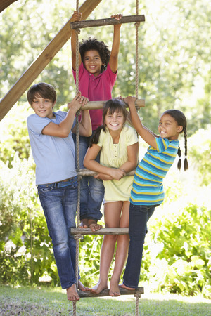 about age: Group Of Children Climbing Rope Ladder To Treehouse