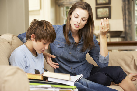 whilst: Mother Becoming Frustrated With Son Whilst Doing Homework Sitting On Sofa At Home Stock Photo