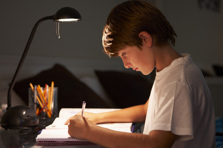 sitting at desk: Young Boy Studying At Desk In Bedroom In Evening