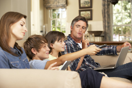 Children Watching TV Whilst Parents Use Laptop And Tablet Computer At Home
