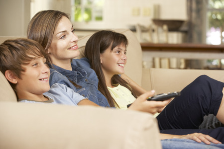 mom: Mother And Two Children Sitting On Sofa At Home Watching TV Together