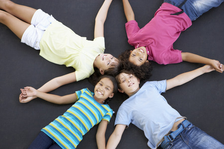 old girl: Overhead View Of Group Of Children Lying On Trampoline Together