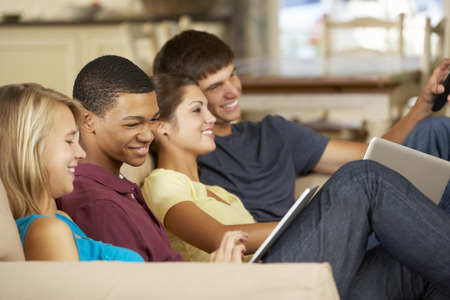 gente viendo television: Cuatro adolescentes que se sientan en el sof� en el pa�s usando el ordenador de la tablilla y la computadora port�til mientras que ve la TV