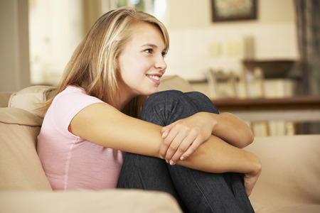teenage girl: Smiling Teenage Girl Sitting On Sofa At Home Watching TV