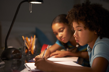 lamp: Two Children Studying At Desk In Bedroom In Evening