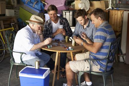 Groep mannelijke vrienden speelkaarten in Garage Stockfoto