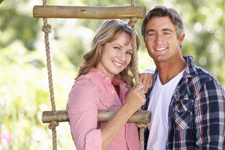 middle aged man: Middle Aged Couple In Garden By Treehouse Stock Photo