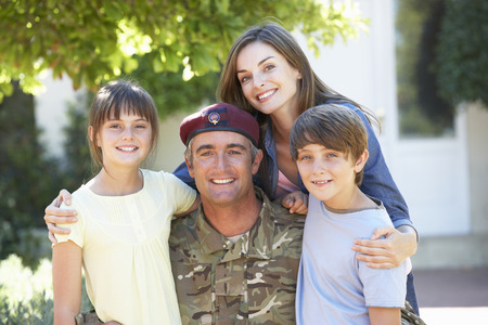 coming together: Portrait Of Soldier Returning Home With Family Stock Photo