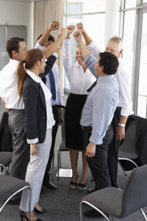 mixed age range: Group Of Businesspeople With Arms Raised At Company Seminar