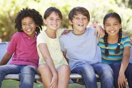 kinder spielen: Gruppe Kinder sitzt am Rand der Trampoline Zusammen