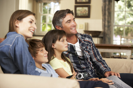family sofa: Family Sitting On Sofa At Home Watching TV Together